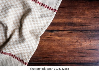 Checkered white and red napkin on an old wooden brown background, top view. Image with copy space. Kitchen table with a towel - top view with copy space.