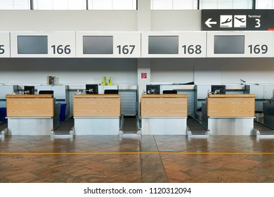 Check-in counters area at international airport Vienna Austria. A lineup of check-in counters with black LCD screen.