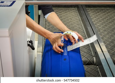 check-in employee attaches a luggage tag to suitcase of passenger - closeup of hands