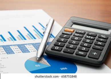 Checking accounting report on business table. Calculator, pen and document with blue charts on wooden desk.