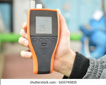 Checking the air condition with the device. Measurement of air temperature and humidity. Part of the image is blurred.