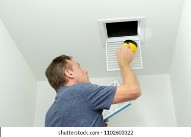 Checking Air Ducts in a Home HVAC System. Man inspecting air ducts shining a flashlight through a small square ceiling vent into ducting pipes. Mature male examining the condition of air ducts at home