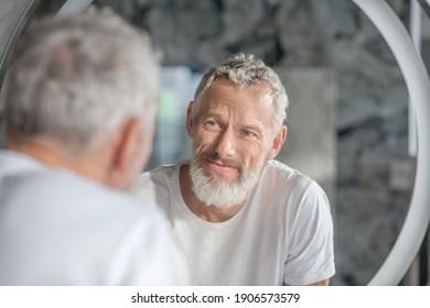 Prüfen eines Aussehens. Ein grauhaariger Mann, der sein Spiegelbild im Spiegel betrachtet