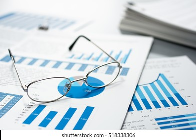 Checking business reports. Glasses and pile of documents. Many graphs and charts. Pile of documents on gray reflection background.