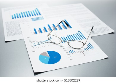 Checking business reports. Graphs and charts. Documents and glasses on gray reflection background.