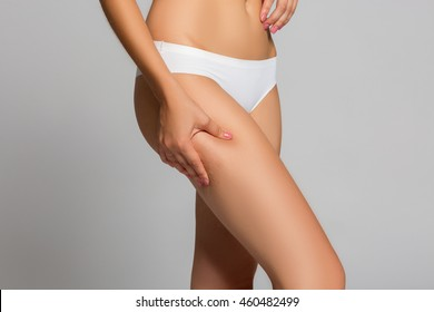 Checking cellulite, woman hip, close up of beautiful female body legs belly, perfect figure isolated over white background