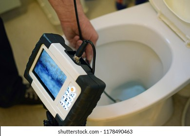 Checking clogged toilet pipe with inspection camera.