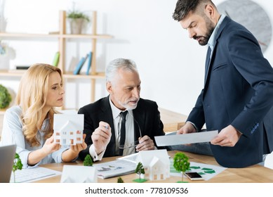 Checking details. Smart qualified real estate agent sitting on the table and looking serious while showing an important document to his reliable experienced colleagues