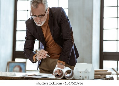 Checking the documents. Interior designer wearing glasses and nice jacket checking the documents