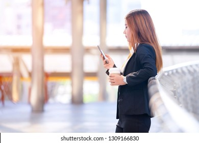 Checking email or text message from smartphone and take break to drink coffee while stand outside office workplace. Modernisation to use online mailbox innovation on mobile with faster communication