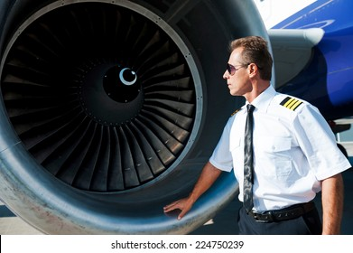 Checking the engine. Confident male pilot in uniform examining turbine engine of airplane