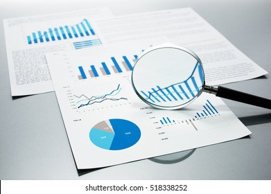 Checking financial reports. Graphs and charts. Documents and magnifying glass on gray reflection background.