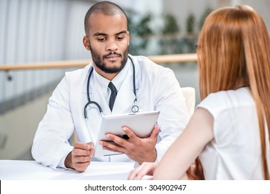 Checking medical tests. Serious doctor and patient. Doctor holding tablet and talking with a patient in the hospital