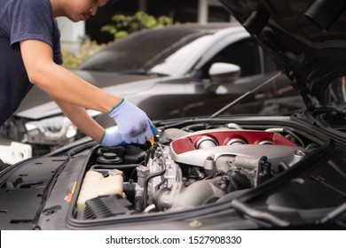 Checking the motor oil for the trip ,The car mechanic staff is pulling the oil level gauge up to check the oil level.