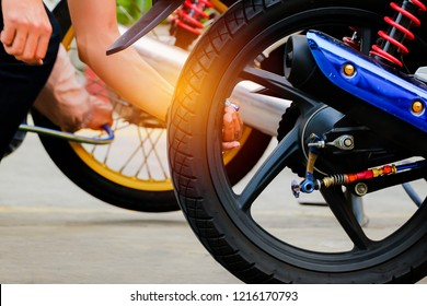 Checking motorcycle tire pressure for safety drive.