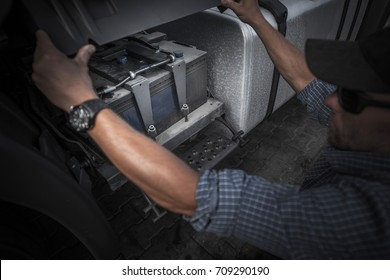 Checking on Truck Battery. Trucking Concept Photo. Caucasian Truck Driver Opening Vehicle Battery Compartment.