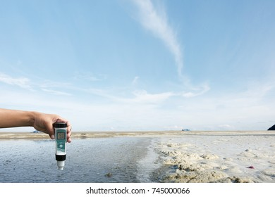 Checking pollution with water quality tester on the beach