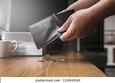 Checking and pour money in leather wallet on the working desk with soft light from outside