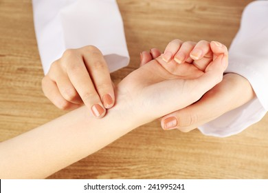 Checking pulse by hand on wooden background