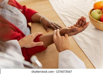 Checking the pulse. Nurse wearing white jacket checking the pulse for woman wearing red cardigan
