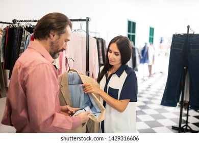 Checking the quality. Attractive dark-haired bearded tall man checking the quality of a blazer suggested by appealing charming beautiful consultant.