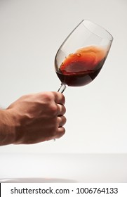 Checking red wine quality isolated on white  background. Elegant red wine glass