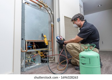 Checking refrigerant charge on a heat pump, wearing a safety mask and glasses