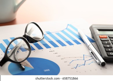 Checking report on business table. Glasses, pen, calculator and document with blue charts on wooden desk.