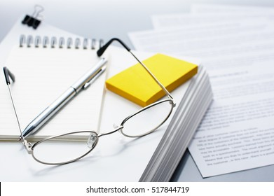 Checking and reviewing documents. Glasses, pen and pile of documents. Pile of documents on gray reflection background.