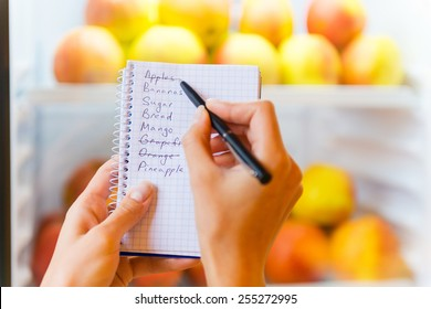 Checking shopping list. Close-up of woman checking shopping list with apples in the background