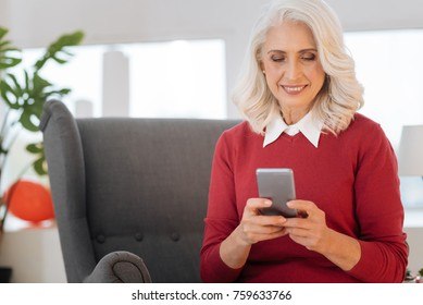 Checking social media. Waist up shot of a joyful senior lady smiling cheerfully while sitting in a chair and reading the latest news on her phone.