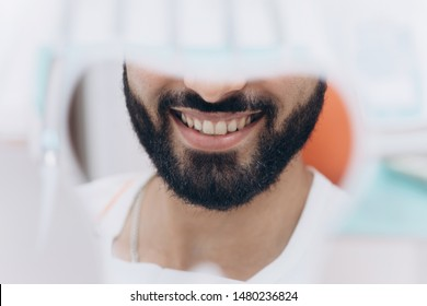 Checking their teeth at mirror after dental treatment. Check out. A mirror in a hand of a nice-looking man with a perfect smile which he is using for checking the final look of his smile