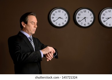 Checking the time. Confident mature businessman looking at his watch while standing in front of the wall with the clocks showing different time