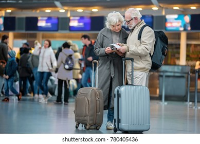 Checking trip details. Full length of serious senior wife and husband are standing with suitcases at international airport and looking at flight tickets with concentration. Copy space in left side