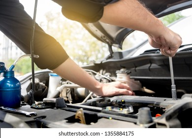 checking vehicle engine at the garage industrial concept, Hands of auto mechanic checking in a car with open hood