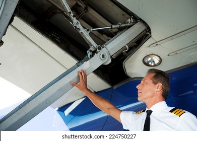 Checking the wing. Low angle view of confident male pilot in uniform examining airplane wing