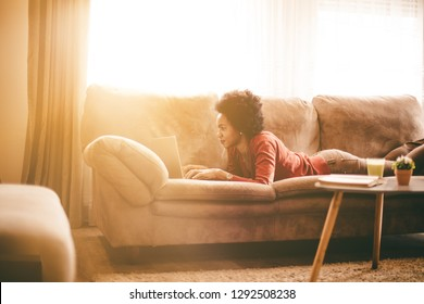 Checking your current obligations for today. African American woman at home using laptop.