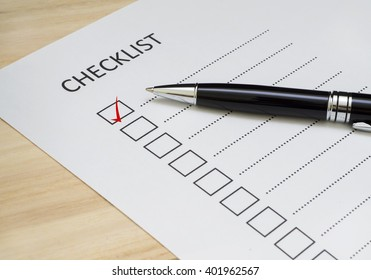 Checklist concept - checklist box with red checkmark, paper and a pen with checklist word on wooden table