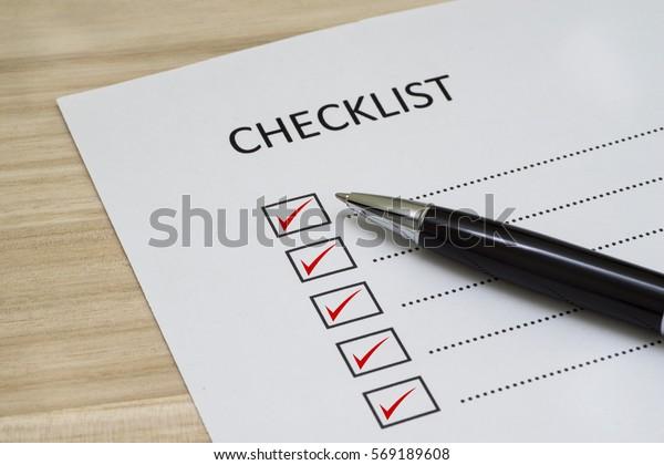 Checklist-Konzept - Checkliste mit rotem Auswahlfeld, Papier und einem Stift mit Markierungswort auf Holztisch
