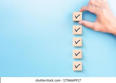 Prüflistenkonzept, Markierung auf Holzblöcken überprüfen, blauer Hintergrund mit Kopierraum
