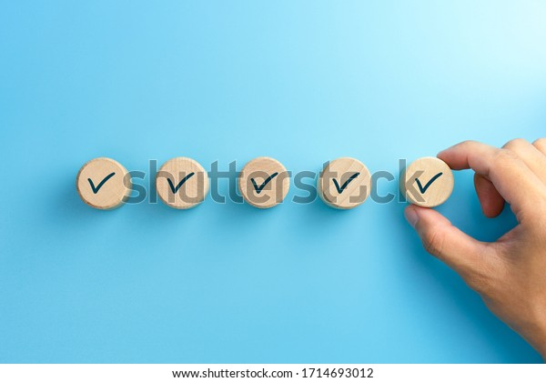 Checklist concept, Check mark on wooden blocks, blue background with copy space