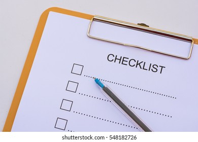 Checklist concept - checklist, paper and a pen with checklist word on wooden table