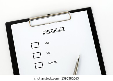 Checklist Form Yes, No, Maybe on attached on Clip board and pen on white background