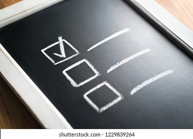 Checklist on chalkboard. Agenda and progress of project in business. Document of finished work duties and responsibilities. Checklist of completed tasks and keeping score of obligations.