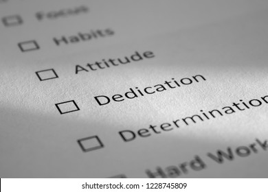 Checklist on a white sheet of paper with points Focus, Habits, Attitude, Dedication, Determination. The inscription Dedication is highlighted by a beam of light and is in focus.