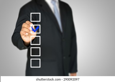 checklist on whiteboard with businessman hand drawing a blue check mark in one checkbox
