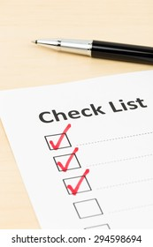 Checklist paper with tick mark and pen