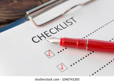 checklist, red pen on a wooden background close-up. business. planning.