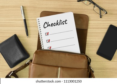 Checklist word written on notebook. Men's leather bag with personal items on wood background.
