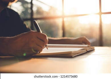 Checklist Writing Notice Remember Planning Concept,home office desk background,hand holding pen and writing note on wood table.